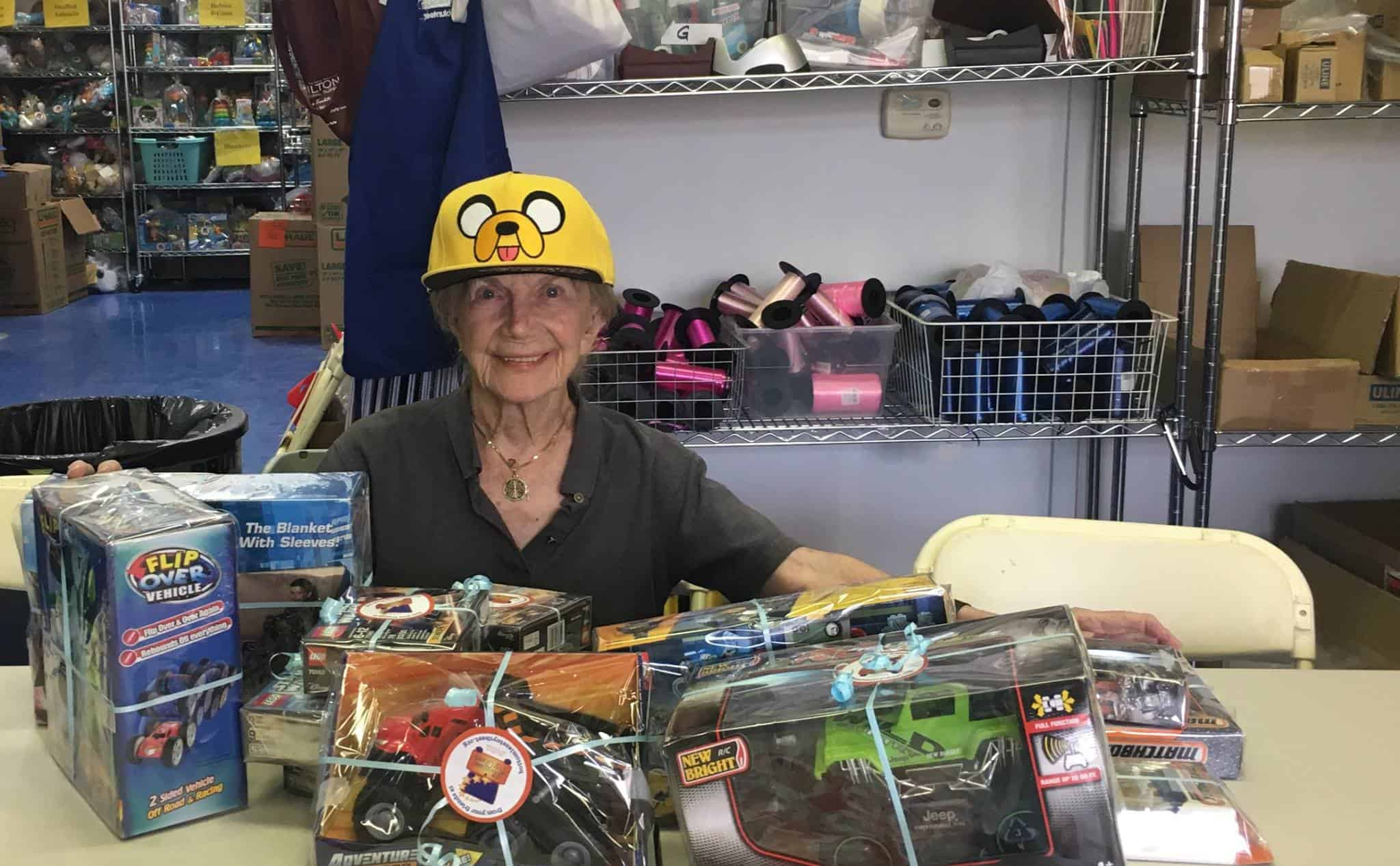 A woman wearing a hat and wrapping gifts.