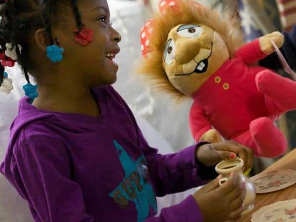 A child smiles with a new stuffed toy.