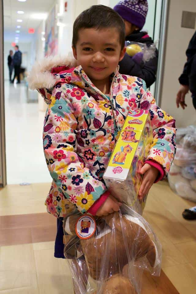 A girl in a colorful coat holding new toys.