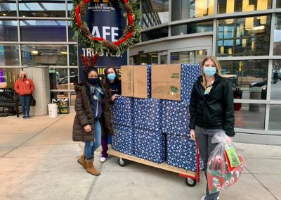 Bottomless Toy Chest staff and volunteers with a stack of toys in front of a hospital.