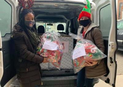 Bottomless Toy Chest volunteers unloading toys from the back of a van.