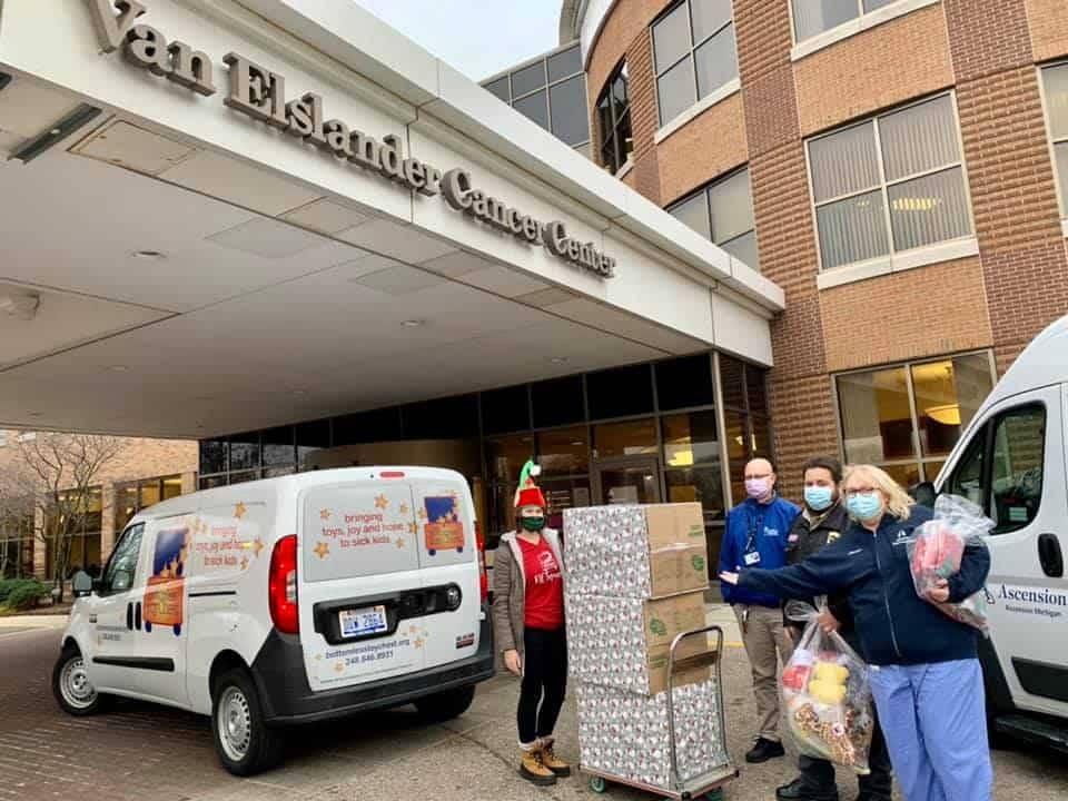 Bottomless Toy Chest staff and volunteers in front of a hospital with boxes of toys to deliver.