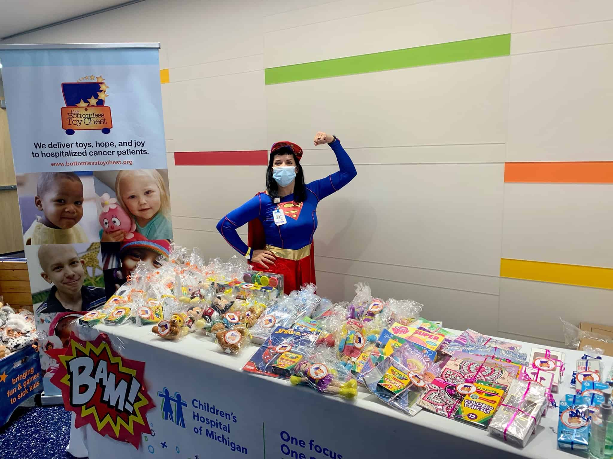 A Bottomless Toy Chest employee dressed as Wonder Woman flexes a muscle while standing near a table of gifts.