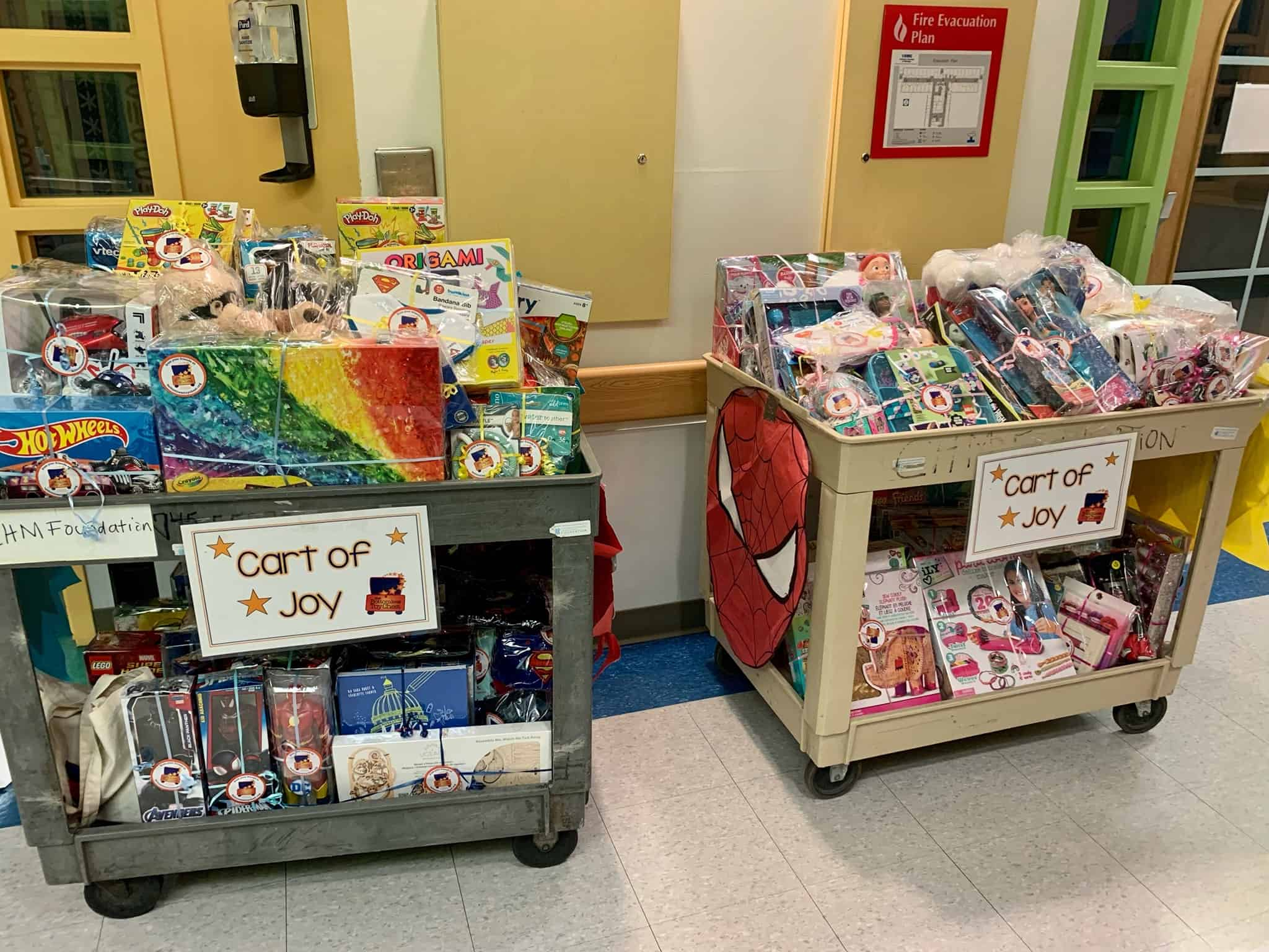 Two carts full of gifts and toys in a hospital hallway.
